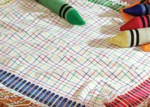 This woven baby blanket is made on an 8-shaft loom to create the crayon motifs.