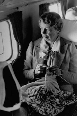 Eleanor Roosevelt gazing out of an airplane window while knitting during a tour of the United States. Photo by Thomas D. Mcavoy/The LIFE Picture Collection/Getty Images.