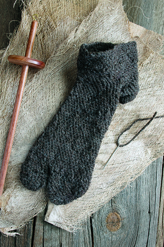 Coptic sock created by Charlotte Booth. She based her instructions on the material developed in a project that re-created socks from the Petrie Museum of Egyptian Archaeology's collection. Included in the photo is a drop spindle that was used in the project to spin some of the fleece and a large-eyed needle threaded with wool—the only material needed to make the sock. Photo by Joe Coca.