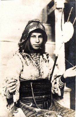 A 1916 postcard shows a young woman in Balkan costume holding a spindle and distaff.