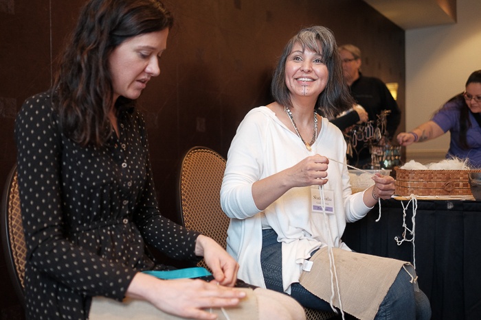 Shaa (right) teaches Ashli Tyre and other attendees the technique of thigh spinning at the Salish Wool Weaver's Symposium. Photo: Kathy Cadigan.